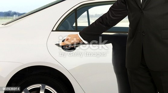 Driver in black suit opening white car door