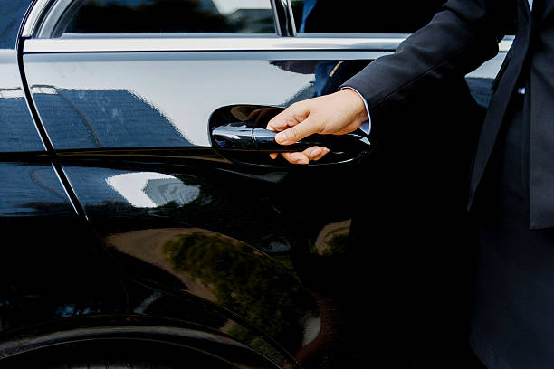 chauffeur open car door - limousine service stock photos and pictures