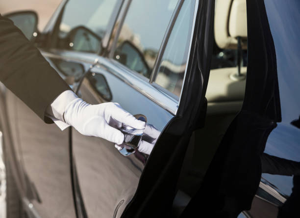 Chauffeur opening car door, close-up of hand