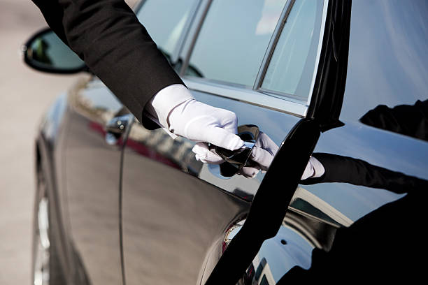 Chauffeur opening / closing luxury car door The white gloved hand of a uniformed chauffeur / doorman opening / closing a luxury car door. high society stock pictures, royalty-free photos & images