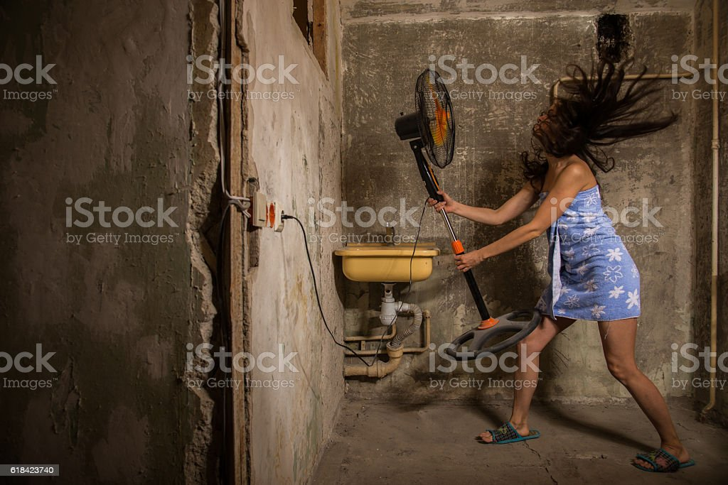 Cheap accommodation. Girl dries hair improvised means stock photo