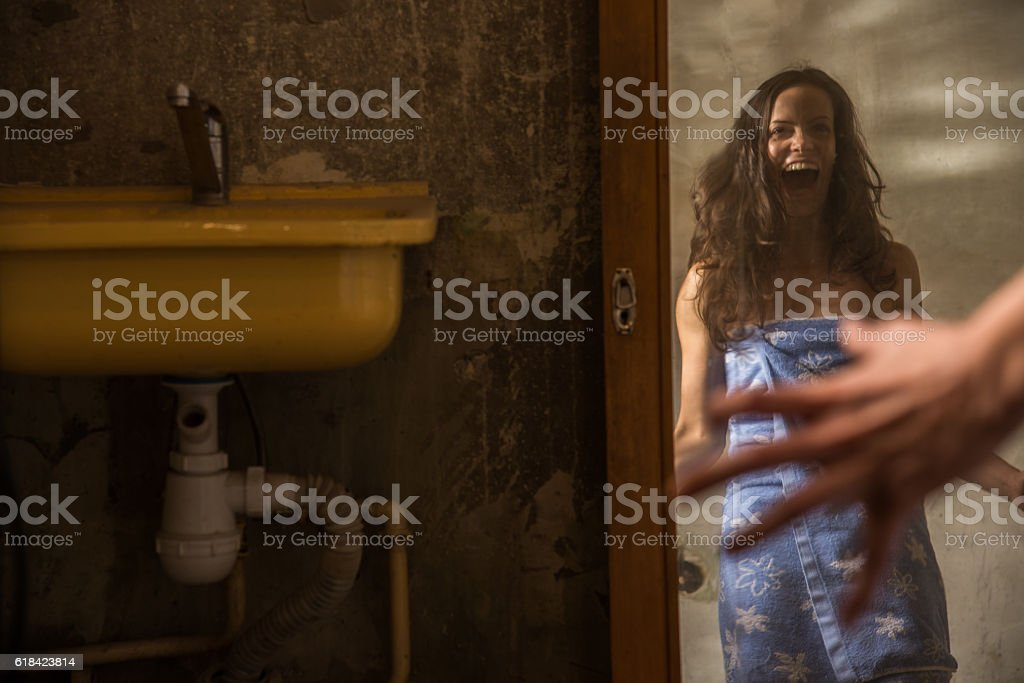 Cheap accommodation. The girl looks into the old distorted mirro stock photo