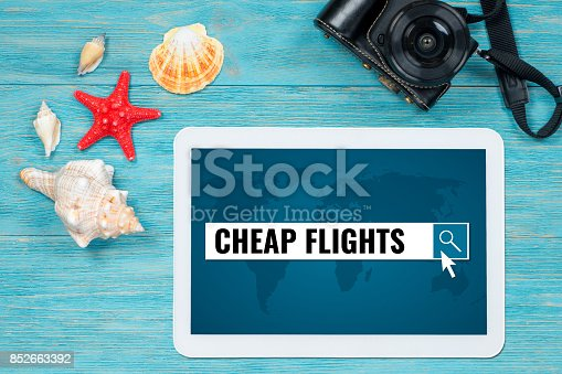 istock cheap flights searching, website page opened in digital tablet lying on turquoise table 852663392