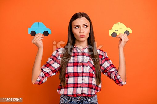 istock Cheap or expensive concept. Close up photo of unsatisfied unhappy pondering planning pensive woman choosing way of traveling holding two different cars in hands isolated background 1180412942