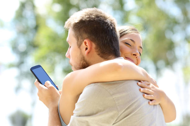 cheater hugging his innocent girlfriend - bad date stock photos and pictures