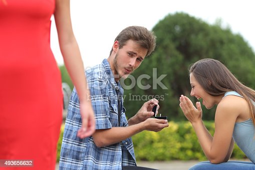 185866319istockphoto Cheater man cheating during a marriage proposal 493656632