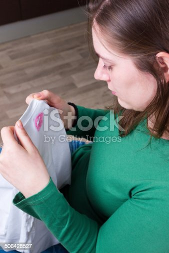185866319istockphoto Cheating proof: lipstic marks on husband's t-shirt 506428527