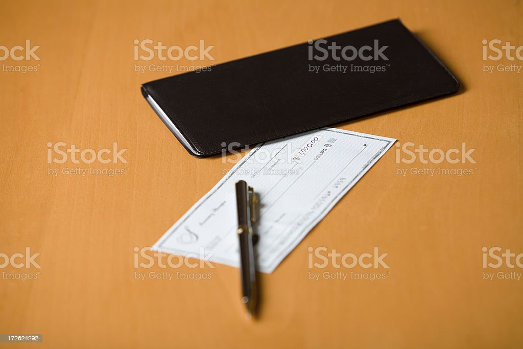 Check and a checkbook on table royalty-free stock photo
