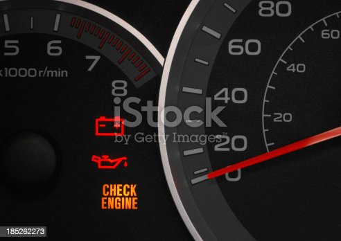 Close up on a cluster with the check engine warning light on indicating a car failure.