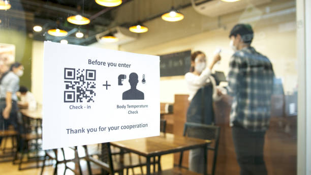 Check in and body temperature check paper sign measure in front of restaurant with staff scan body temperature and scan QR code for check in. New normal for protection covid-19 after reopening. stock photo