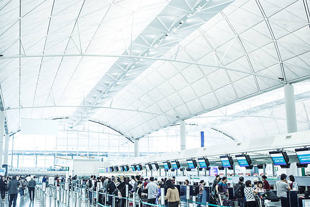 check in at hong kong international airport - airport terminal stock photos and pictures