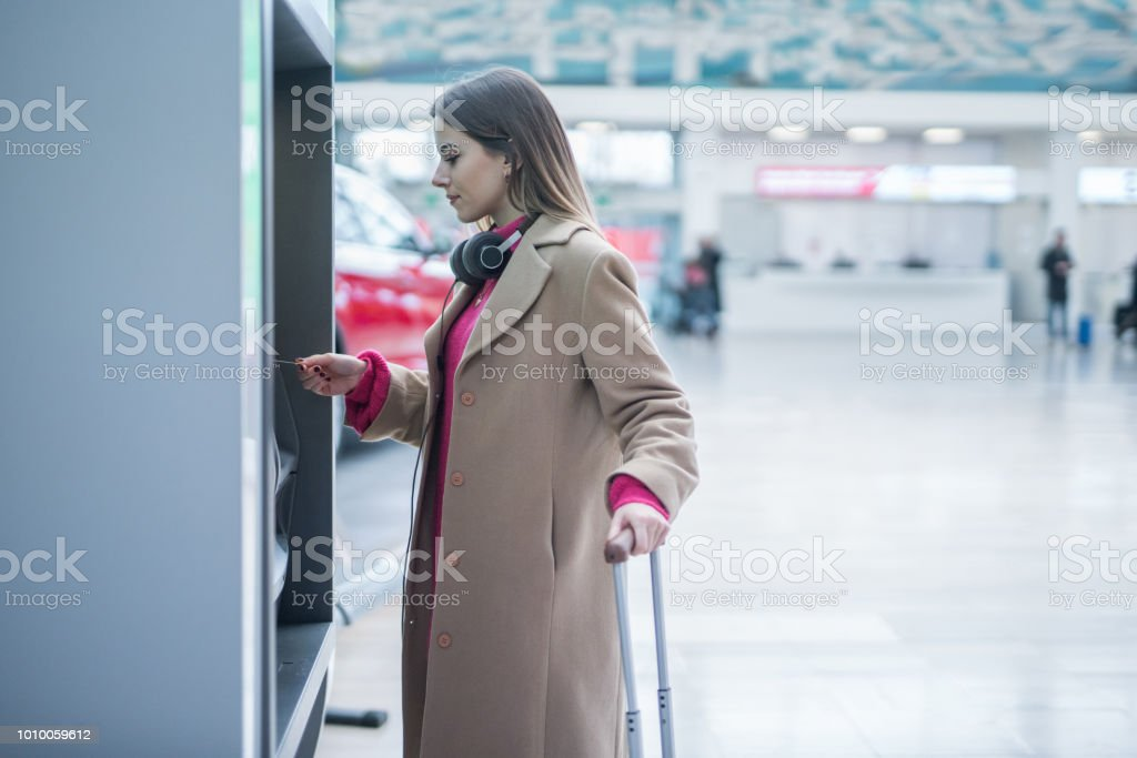 Young businesswoman taking money from the atm at the airport
