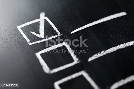 istock Check list on blackboard macro close up. Document of finished work duties and responsibilities. Agenda and progress in business. Checklist, keeping score of obligations or completed tasks. 1124733034