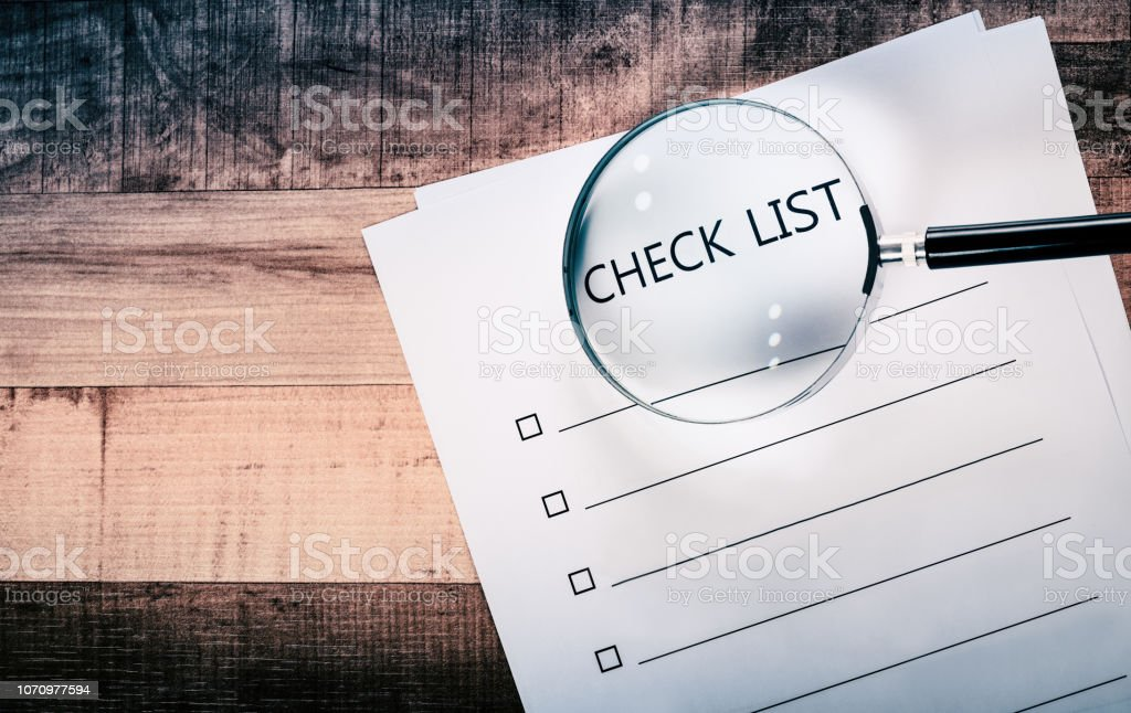 check list sheet and magnifying glass on desk.