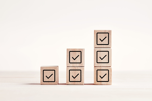 Check mark on wooden blocks against blue background with copy space. Checklist concept.