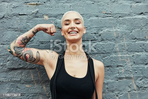 Cropped portrait of an attractive young woman flexing her biceps while working out against a gray background