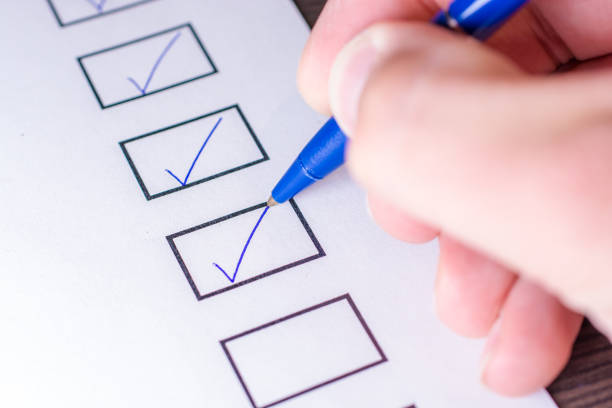 check off the tasks of a to do list with a pen - checklist stock photos and pictures