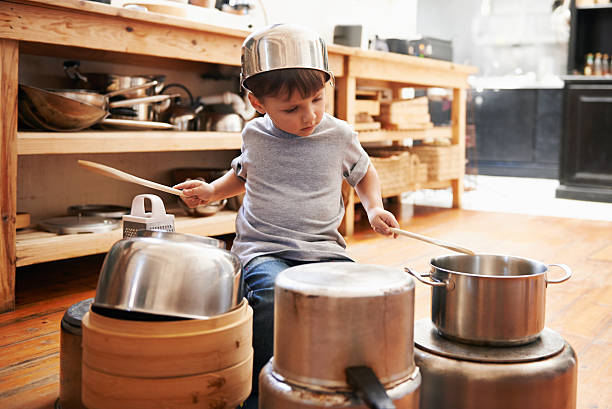 Check out my awesome drumming technique! A young boy playing drums on pots and pans drummer stock pictures, royalty-free photos & images