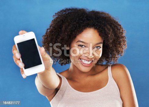 A pretty young woman showing you her smartphone while isolated on a blue background