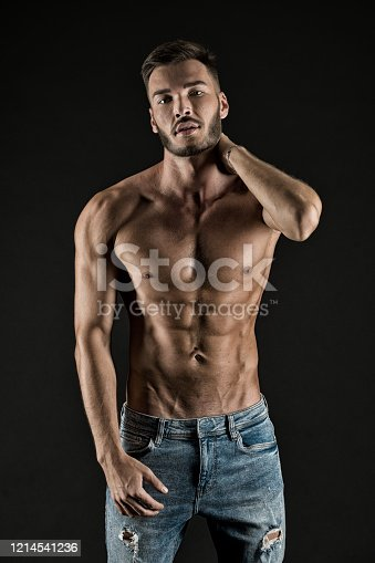 Check out my shape. Man muscular torso tense muscles veins denim pants. Macho muscular chest looks attractive black background. Athlete with muscular body on confident face proud of his shape.