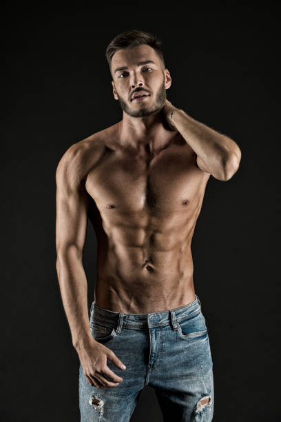 Check out my shape. Man muscular torso tense muscles veins denim pants. Macho muscular chest looks attractive black background. Athlete with muscular body on confident face proud of his shape stock photo