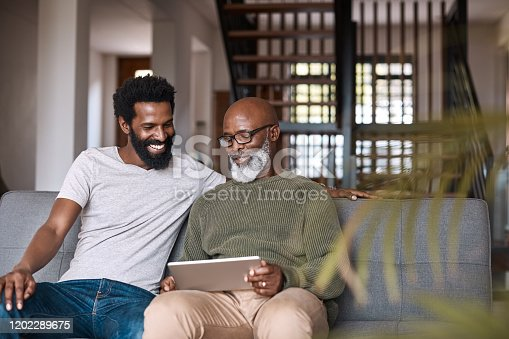 Shot of a happy senior man using a digital tablet while spending some time with his adult son at home
