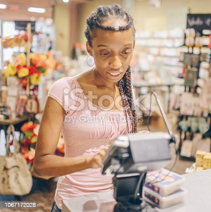 African American woman uses an electronic check out terminal to pay for purchases in a shop. Credit card machine and a woman paying for purchases, shopping trip