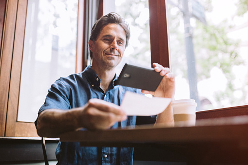 A mature smiling man in his mid 40's takes a picture with his smart phone of a check or paycheck for digital electronic depositing, also known as