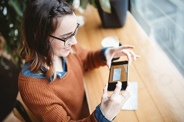 verifica deposito di acquisizione remota al cafe - dispositivo informatico portatile foto e immagini stock