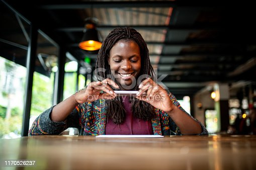 Young African woman making a photo of a check at the bar