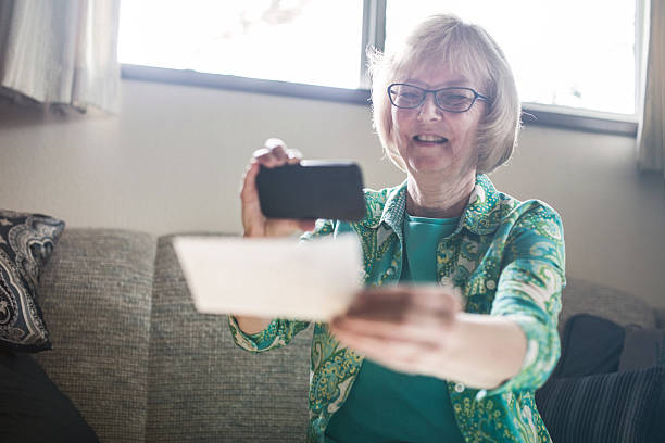 """Check Remote Deposit Capture by Senior A smiling senior woman in her 60's takes a picture with her smart phone of a check or paycheck for digital electronic depositing, also known as """"Remote Deposit Capture"""".  She sits in comfort of her home living room.  Horizontal image. bank deposit slip stock pictures, royalty-free photos & images"""