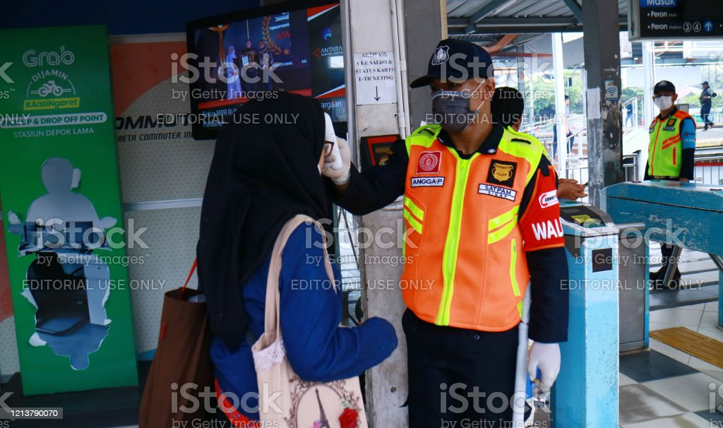 Check the Body Temperature Depok, Indonesia - March 18, 2020: Security officers check the body temperature of passengers at the entrance of Depok Railway Station to prevent the spread of Covid-19. Activity Stock Photo