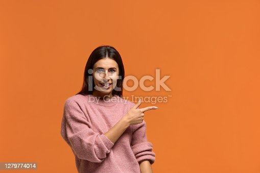 Check this out. Pretty young joyful female points with fore finger away, indicates copy space on blank wall, isolated over yellow background. Wears in pink knitted sweater isolated over orange background