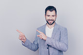 istock Check this out! Young handsome brunet bearded businessman lawyer in grey jacket stands on pure light background, shows at the copy space near him. Advertising concept 935410960