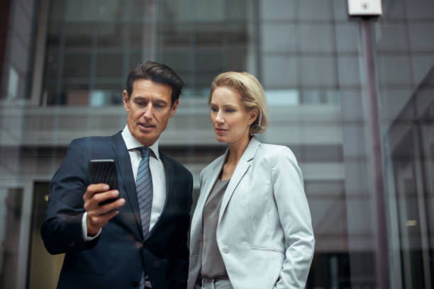 Check this please Two formally dressed executives are working together in the bright office. They are looking at the smart phone. georgijevic frankfurt stock pictures, royalty-free photos & images