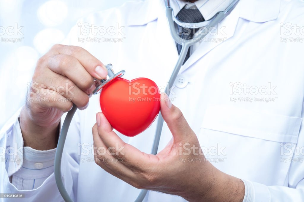 check up on a red heart ball on blur office in the hospital and bokeh background. Concept of health care. stock photo