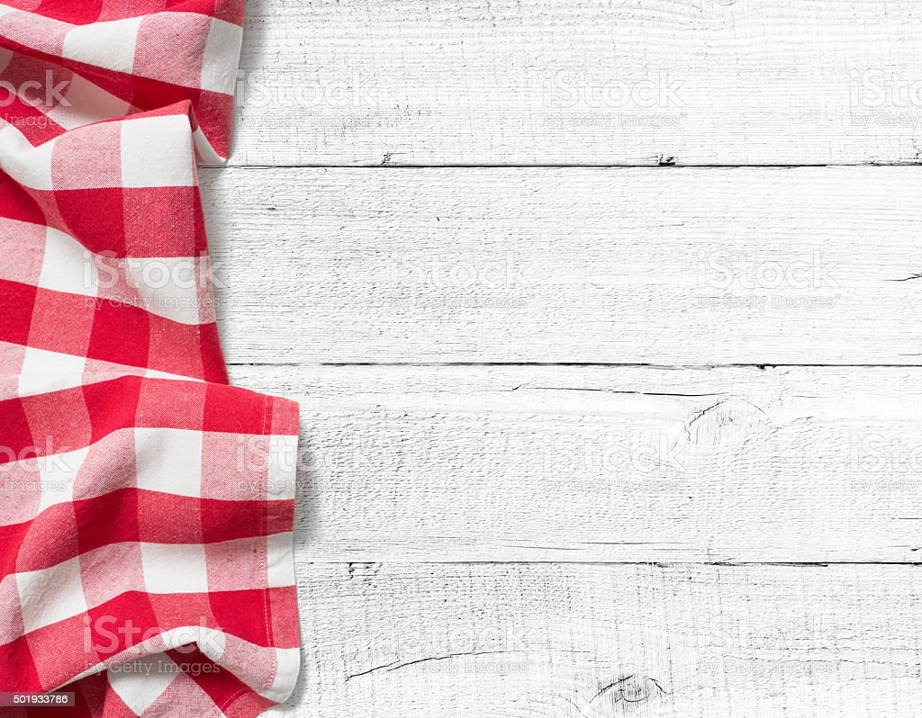 checked picnic tablecloth on white wood table background stock photo