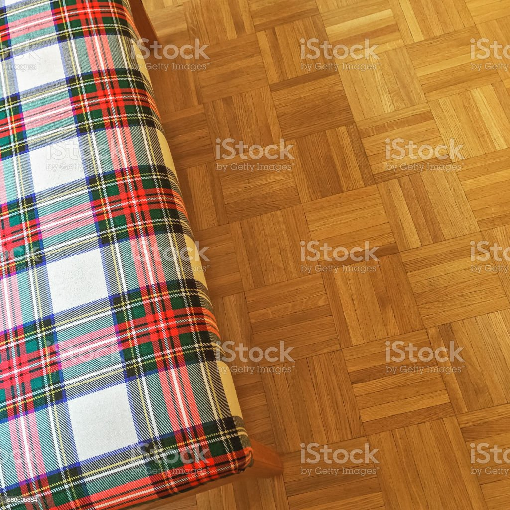 Checked textile banquette on parquet floor zbiór zdjęć royalty-free