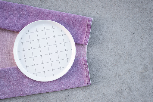 Checked white plate and lilac tablecloth