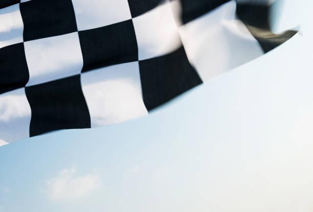 karierte flagge auf blauem himmel - rally stock-fotos und bilder