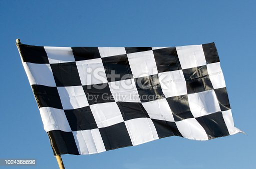 istock Checkered flag isolated on blue sky background 1024365896