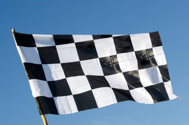 푸른 하늘 배경에서 분리 하는 바둑판 무늬 깃발 - formula 1 뉴스 사진 이미지
