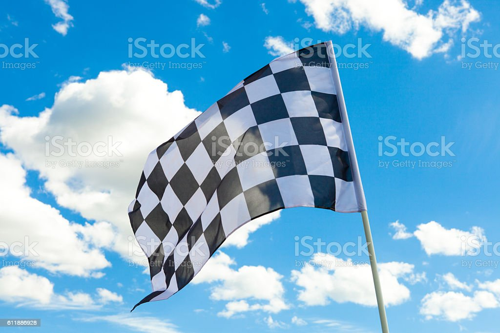 Checkered flag on flagpole with white clouds on background stock photo