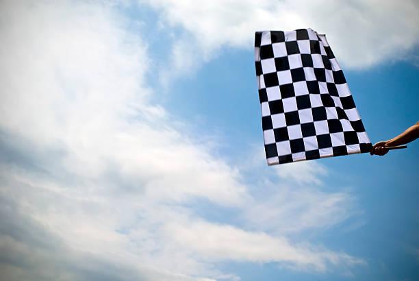 Checkered flag waving under a blue sky stock photo
