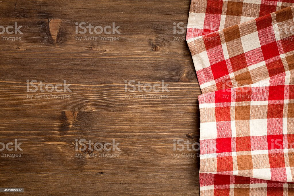 Checkered napkin at right side  of wooden background stock photo