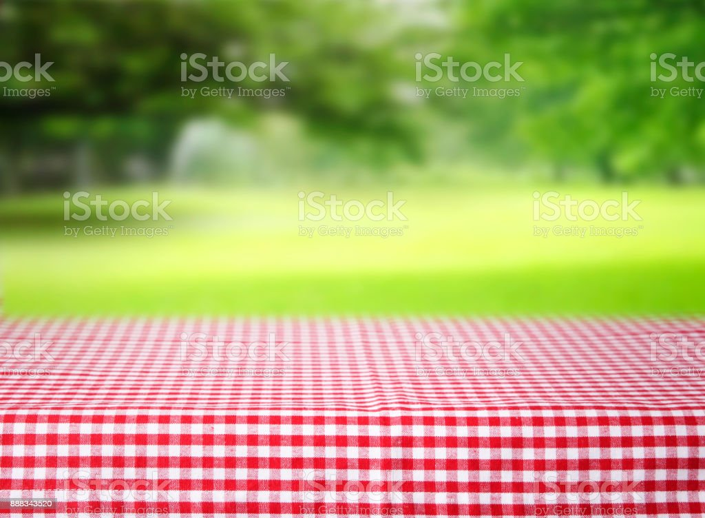 Checkered red tablecloth emty space table green background. stock photo