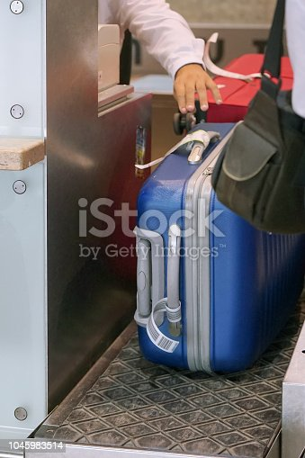 istock check-in at the airport. The airport employee registers the luggage. 1045983514