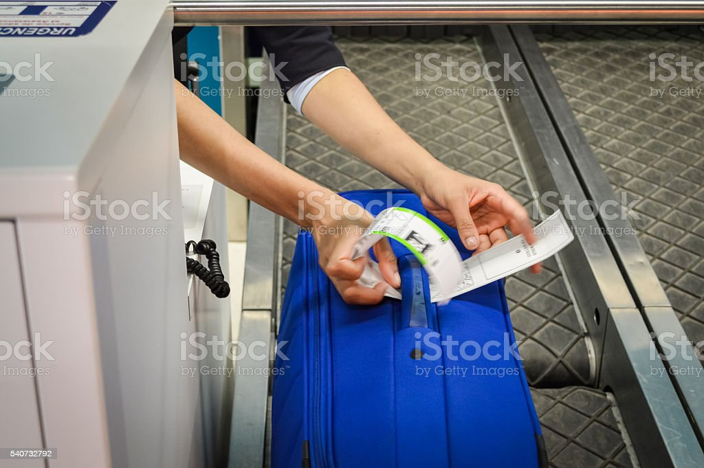 check-in employee attaches a luggage tag stock photo