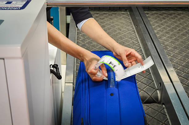 check-in employee attaches a luggage tag - airport check in counter stock pictures, royalty-free photos & images
