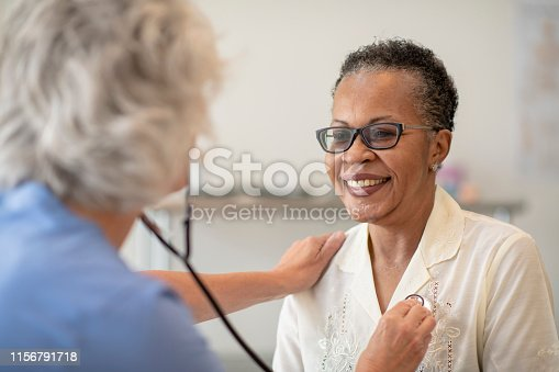 A senior black women is having her heart checked by a female doctor. The patient is wearing glasses and smiling at the doctor. The doctor is wearing scrubs and checking the patients heart rate with a stethoscope.